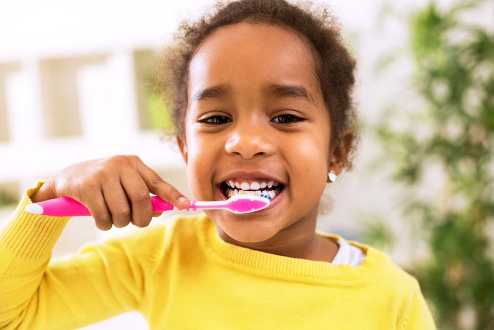 child brushing her teeth with a smile